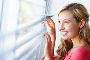 A beautiful young woman looking out at the day through a window